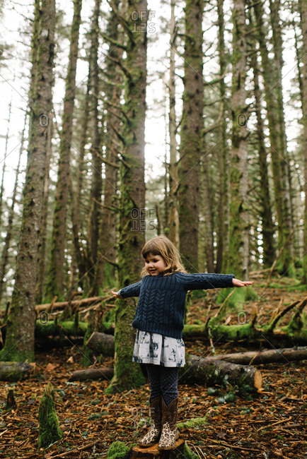 Little girl standing on a tree stump in the woods with her arms outstretched