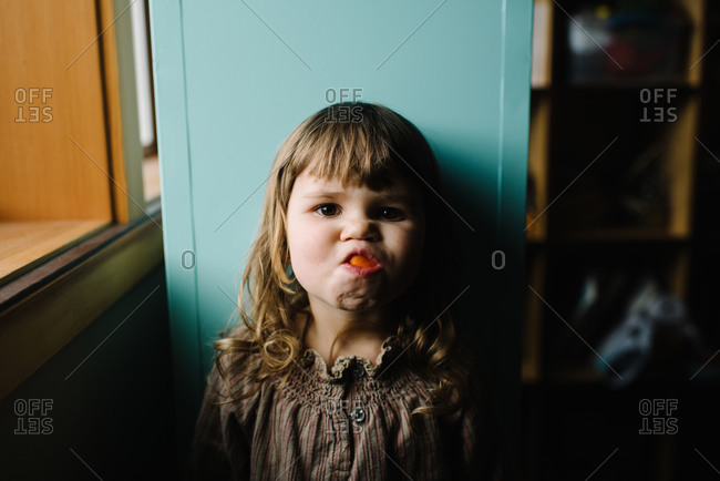 Little girl making a silly face with an orange peel in her mouth