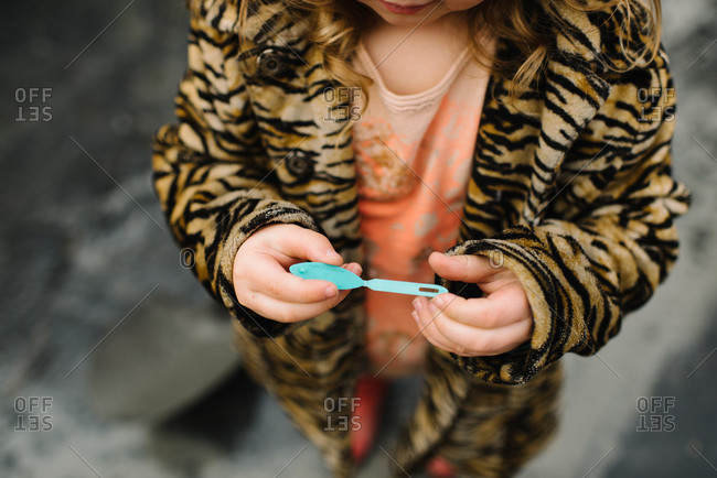 Little girl in a tiger print coat holding a blue plastic hair bow