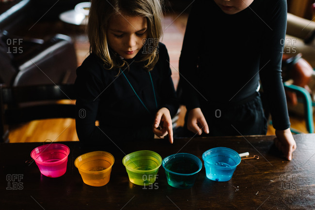 Brother and sister standing at a table with multi-colored dyes