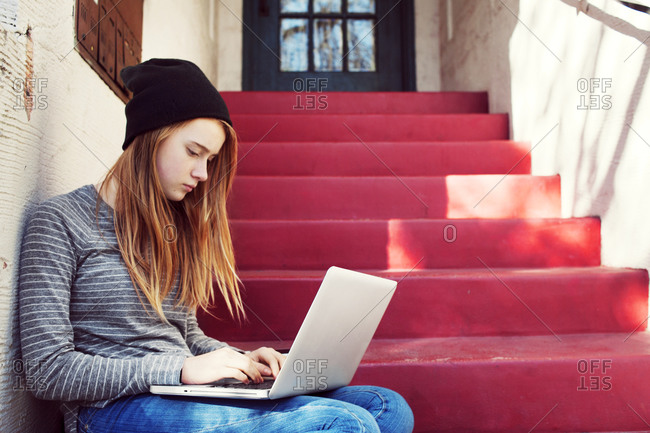 Woman on steps using laptop