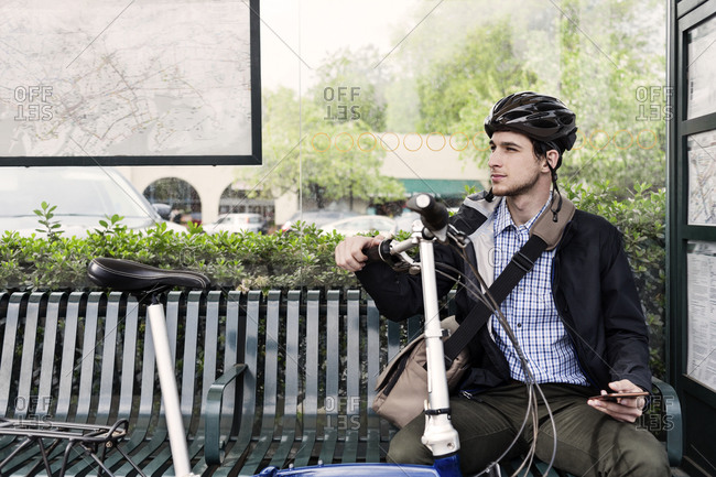 Cyclist at bus stop with cell phone