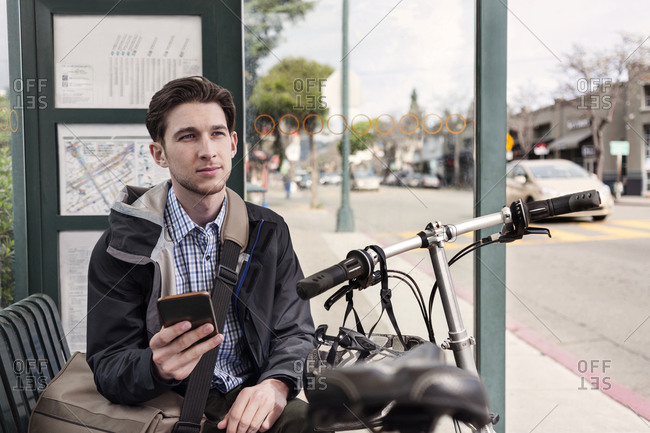 Man at bus stop with cell phone