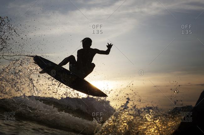 Surfer midair in silhouette