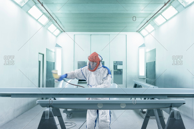 Portrait of worker paint spraying parts on automotive production line