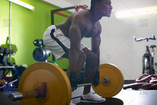 Bodybuilder lifting barbell in gym