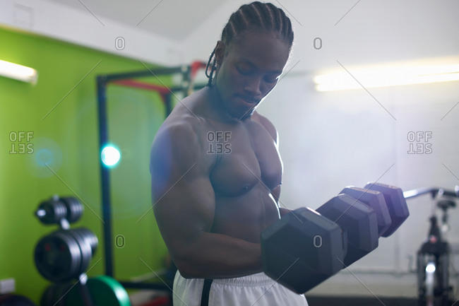 Bodybuilder lifting dumbbell in gym
