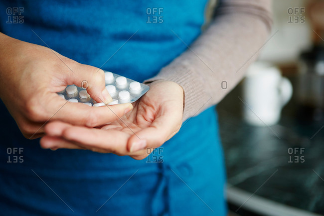 Young woman taking medication from blister pack, close-up