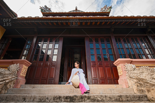 Low angle view of mid adult woman wearing ao dai dress with conical hat sitting on steps in front of imperial palace doorway looking away, Hue, Vietnam