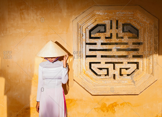 Mid adult woman wearing ao dai dress and conical hat standing in front of wall looking down, Hue, Vietnam