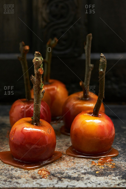 Toffee apples on sticks hardening on marble surface
