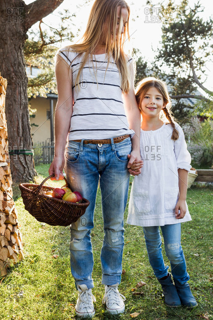 Mother and daughter holding hands, mother holding basket of apples