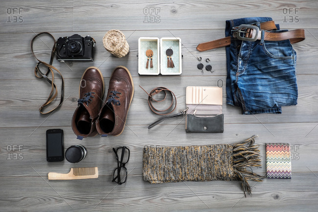 Overhead view of variety of objects including camera, jeans and smartphone