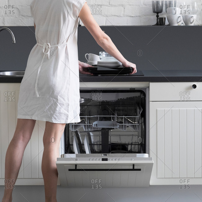 Rear view of woman loading dishes into dishwasher