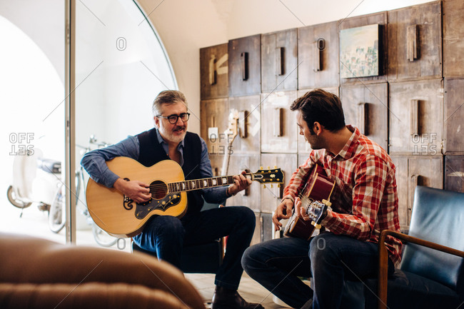 Father and adult son playing guitar in living room