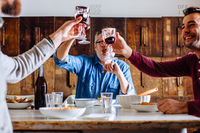 Mature man and adult sons raising a glass of red wine at dining table
