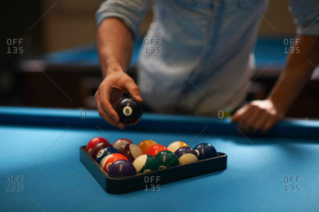 Man arranging balls into triangle on pool table