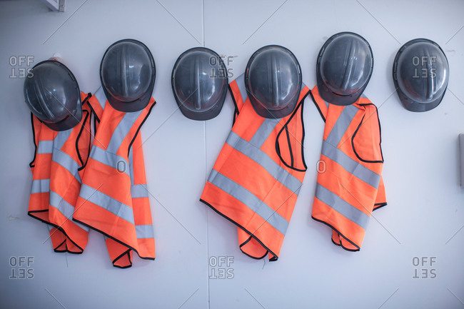 Rows of hard hats and high vis jackets on portable cabin wall