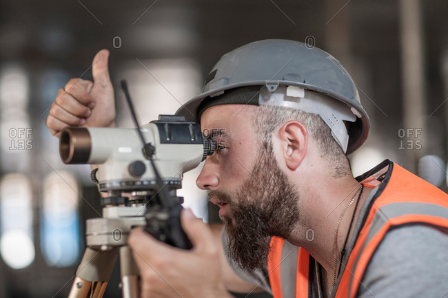 Close up of a young male surveyor looking through theodolite giving thumbs up on construction site