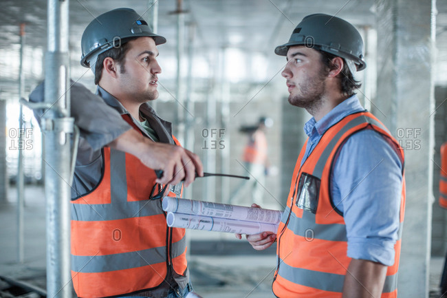 Site manager and builder discussing blueprint on construction site