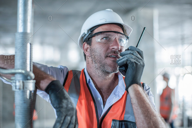 Mid adult male site manager using walkie talkie on construction site