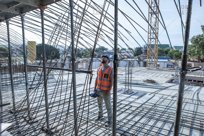 Site manager looking up at steel rod structures on  construction site