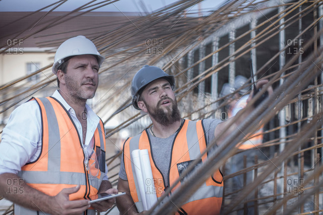 Site manager and builder discussing steel rod structures on construction site