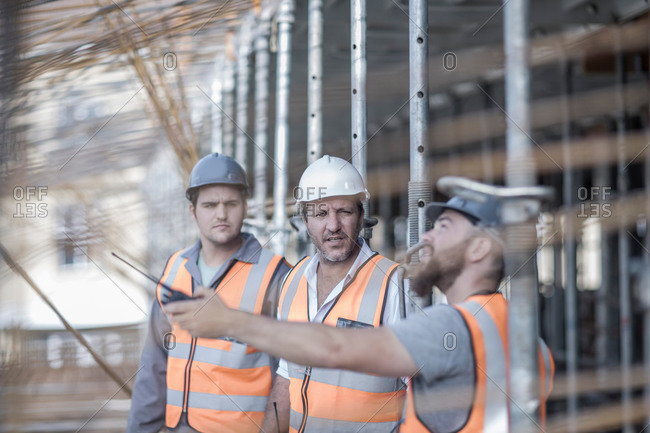 Site manager and builders pointing to steel rods on  construction site