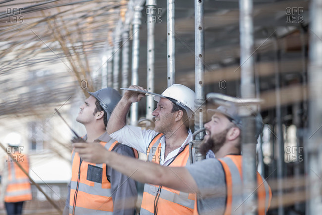 Site manager and builders looking up at steel rod structure on  construction site