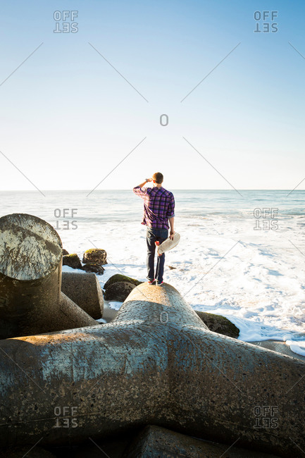 Young man holding skateboard, standing on breakwater, looking towards ocean, rear view