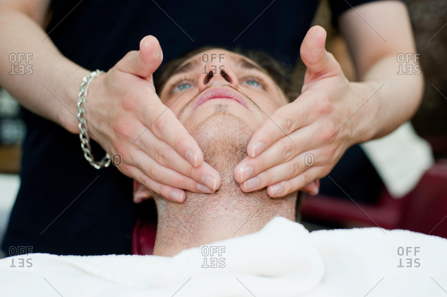 Head and shoulders of young man, head back, having facial massage