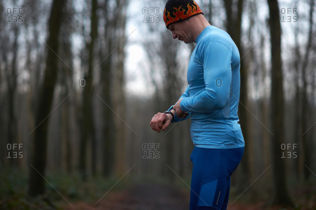 Runner wearing knit hat and spandex looking down at wrist watch