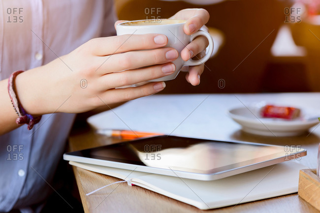 Hands of young woman holding coffee cup using digital tablet