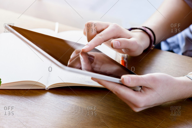 High angle view of young woman's hands using digital tablet