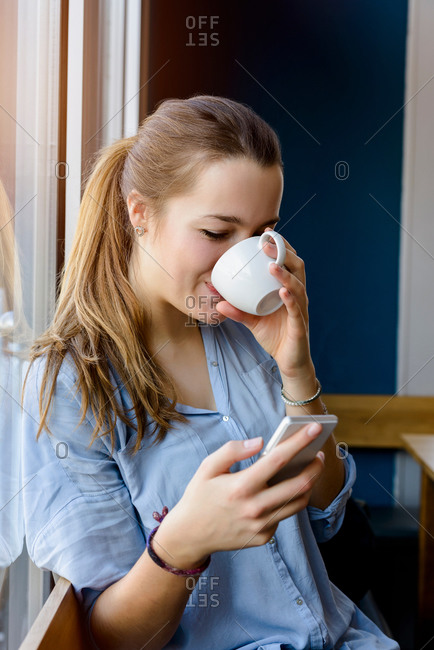 Young woman holding smartphone drinking coffee