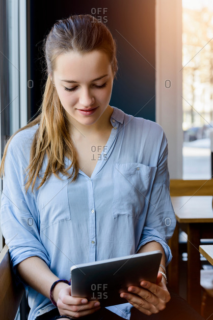 Young woman looking down using digital tablet