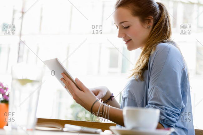 Side view of young woman in cafe looking down using digital tablet