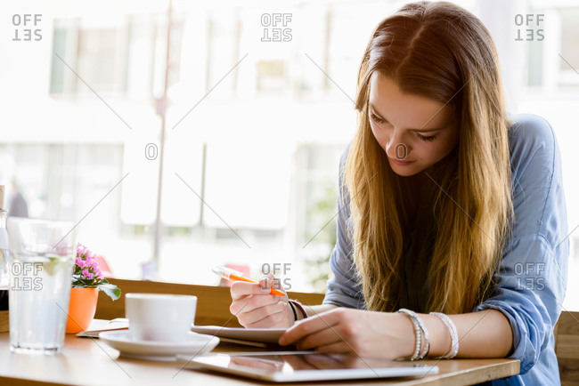 Young woman in cafe looking down writing