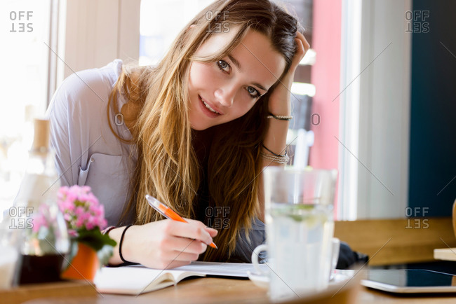 Young woman in cafe writing, hand on head resting on elbow looking at camera smiling