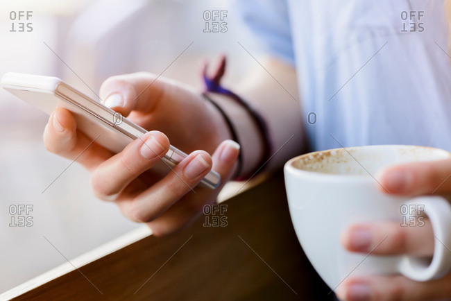 Cropped view of young woman's hands holding coffee cup using smartphone