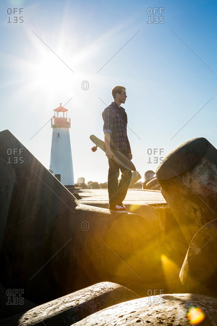 Young man holding skateboard, standing on breakwater near lighthouse