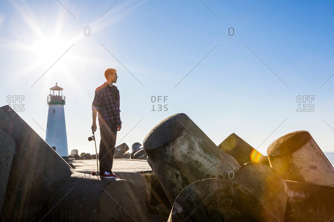 Young man holding skateboard, standing on breakwater near lighthouse, looking towards ocean