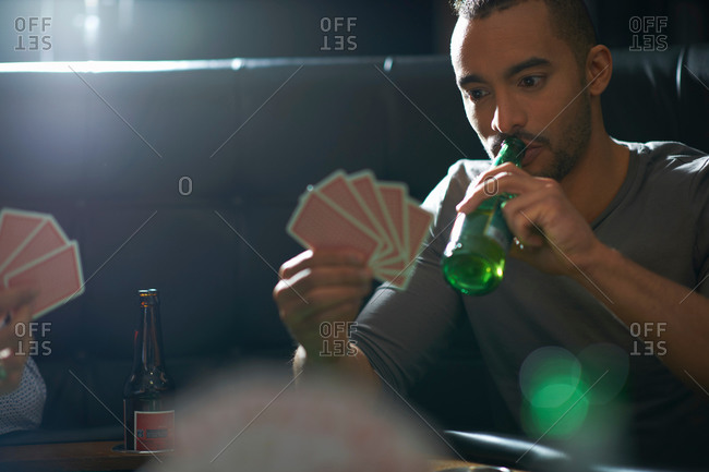 Male friends drinking beer and playing card game at pub card table