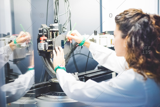 Female scientist positioning thin film sample on sample holder on x-ray diffractometer