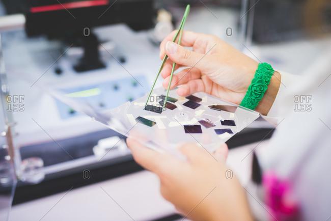 Female scientist using FTIR spectrophotometer, taking thin film sample for measurement