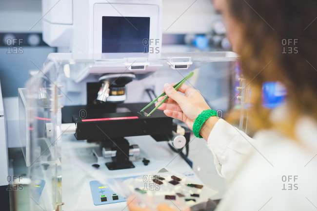 Female scientist using FTIR spectrophotometer, positioning thin film sample on microscope stage