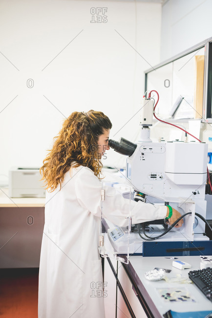 Female scientist using FTIR spectrophotometer, looking at thin film sample through the FTIR microscope