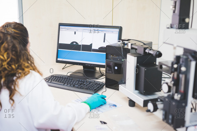 Female scientist analyzing obtained contact angle data