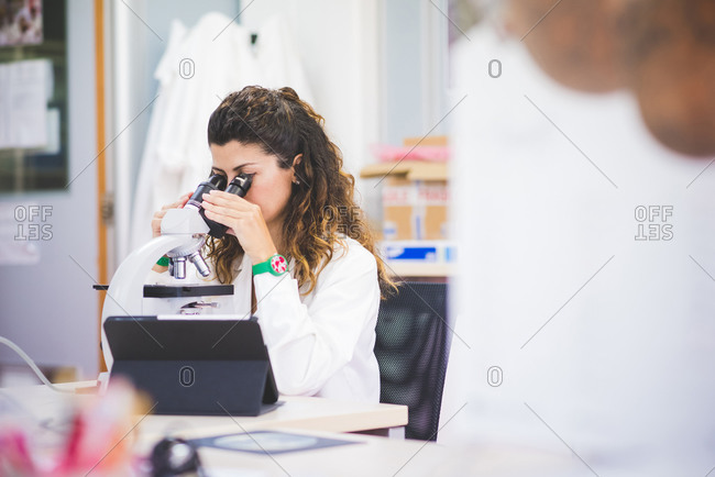 Female scientist analyzing surface material by using optical microscope