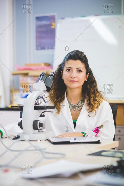 Female scientist using optical microscope